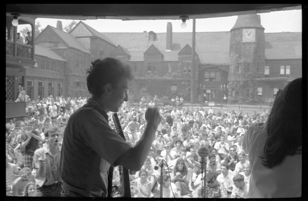 Bob Dylan and Joan Baez walking off stage after their set on Porch #1, Newport Folk Festival: View from stage right, with stands in the background: , July 27, 1963