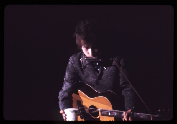 Bob Dylan performing on stage: grabbing a cup of water: Dylan in concert at the Washington Coliseum: , ca. November 28, 1966