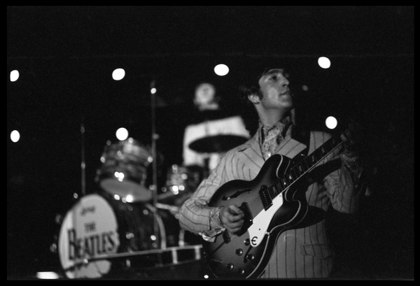 John Lennon performing with the Beatles at D.C. Stadium: Half-length portrait with Ringo's drum kit in the background: , August 15, 1966