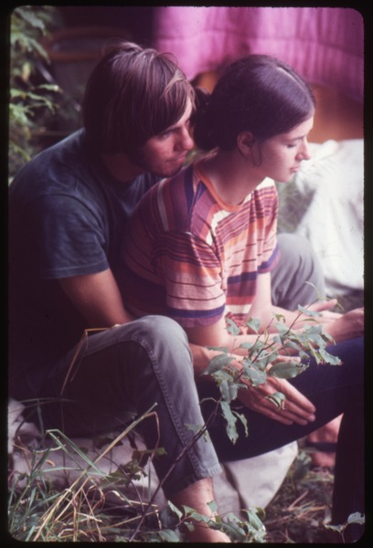 Young couple huddled on the grass, Woodstock Festival, August 17, 1969