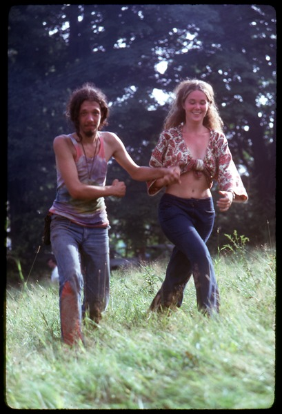 Hippie couple in tie-dye and Indian print, cavorting through the fields, Woodstock Festival, August 17, 1969