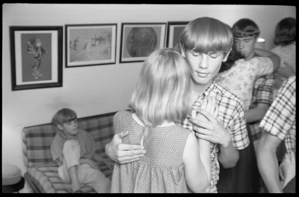 Teenage long hair: boys and girls at a teenage dance party as a young boy             watches from the couch, ca. 1965