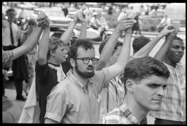 Assembly of Unrepresented People protesters join hands and raise their arms             during anti-war march, August 6, 1965