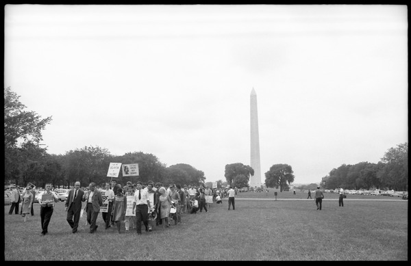 Marchers on the National Mall carrying anti-war signs, heading toward the U.S.             Capitol building (Washington Monument in the background): David Dellinger (front left) being interviewed by news media and Staughton             Lynd (with bullhorn) at head of march: , August 6, 1965