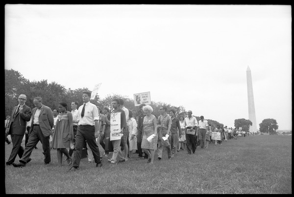 Marchers on the National Mall carrying anti-war signs, heading toward the U.S.             Capitol building (Washington Monument in the background): David Dellinger (front left) being interviewed by news media and Staughton             Lynd (front right) at head of march: , August 6, 1965