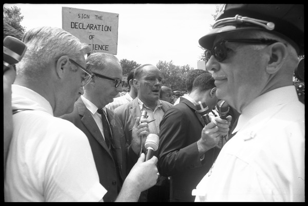 David Dellinger (center) being interviewed by the press after the Assembly of Unrepresented People peace march was             attacked with red paint by right wing counterprotesters, August 6, 1965