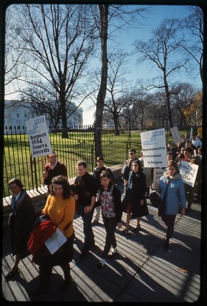Antiwar protesters march past the white house with signs reading 'Steps to             peace... respect 1954 Geneva Accords' and 'Steps to             peace... representative government in Saigon': Washington Vietnam March for Peace, November 27, 1965