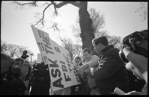 Counter-protesters opposing the antiwar march, struggling over a sign reading             'Ask the FBI and the police', news media looking on: Washington Vietnam March for Peace, November 27, 1965