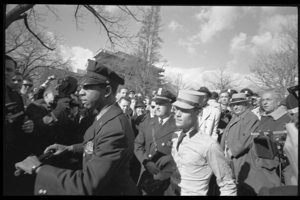 American Nazi Party counter-protester Douglas L. Niles, in             uniform, escorted by police through the crowd: Washington Vietnam March for Peace, November 27, 1965