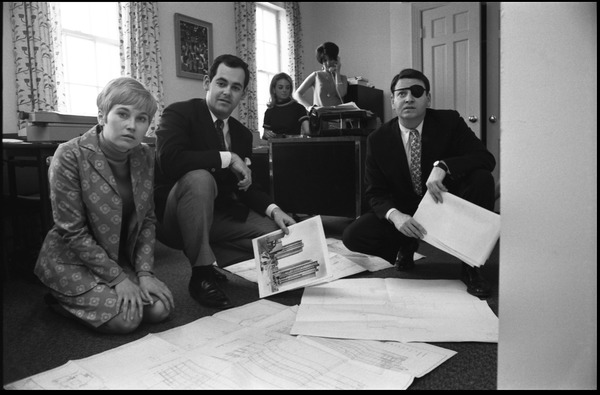 Michael O'Harro (left center) and staff looking over architectural plans in the JOPA club office, ca. May 1967