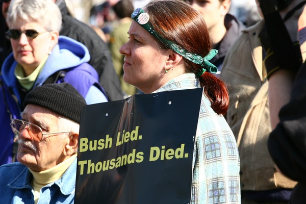 Woman protester holding a sign reading 'Bush lied. Thousands died': rally and march against the Iraq War, March 19, 2005