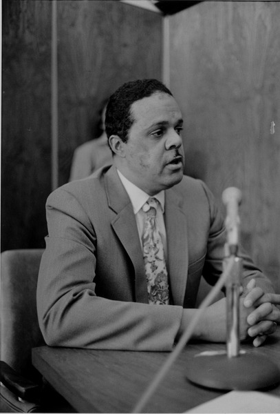 Randolph Bromerey sitting at a table speaking into microphone, April 15, 1972