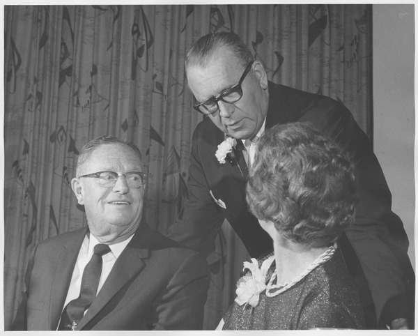 Earl Eastman Lorden and wife Marian Lorden sitting indoors, speaking to Warren             P. McGuirk at 1966 Testimonial Dinner for Earl Lorden, 1966