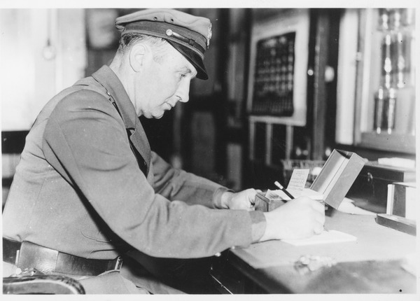 Campus police officer Tom Moran at a desk writing, ca. 1935