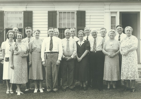 Male members of the class of 1904 and their wives standing in front of a house, 1929