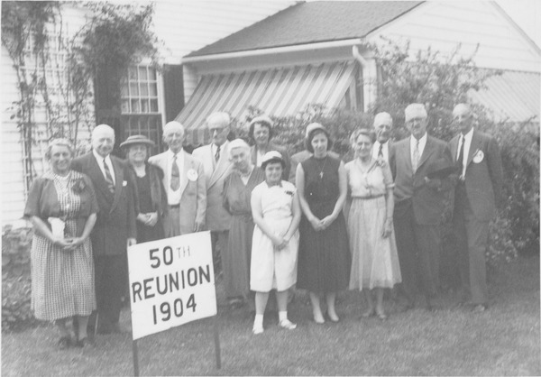 Members of the class of 1904 and their family standing outside a house, 1954