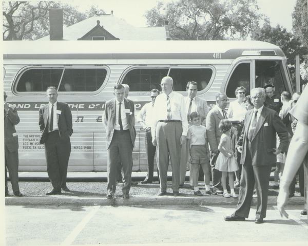 Alumni Medal recipients and family stand in front of a bus during Centennial Alumni weekend, June 7, 1963