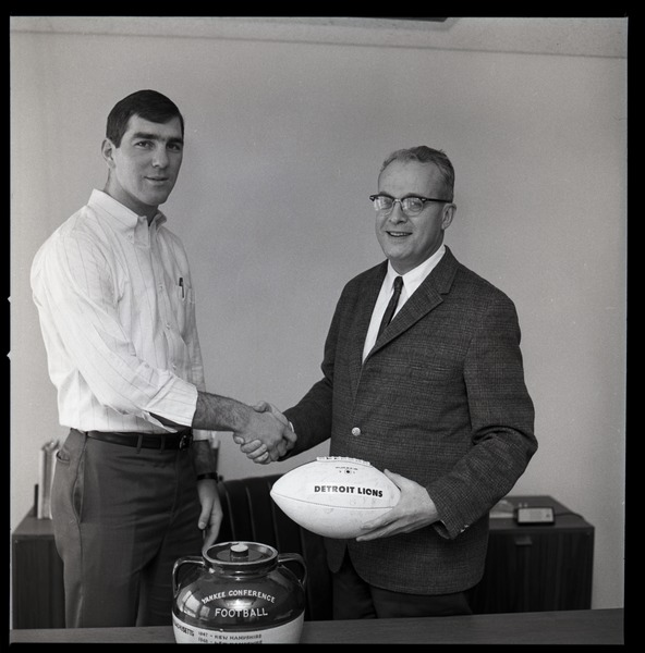 Greg Landry (UMass Amherst football quarterback) shaking hands with University         of Massachusetts President John W. Lederle, with ceremonial football and Yankee Conference Trophy, February 1, 1968