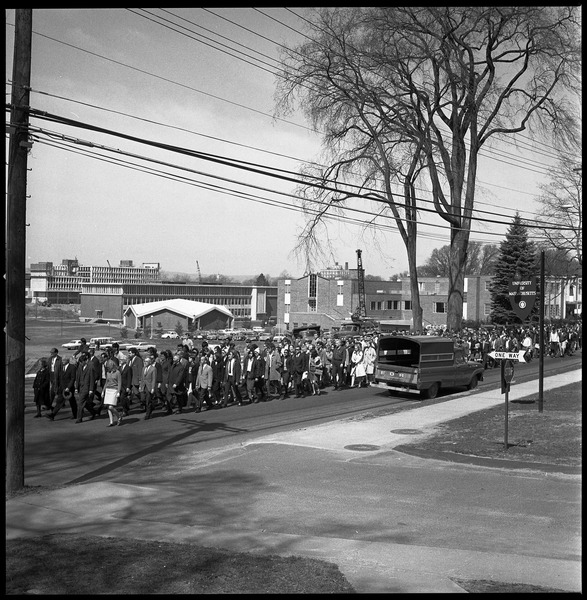Memorial march for Martin Luther King., Jr., led by Linus Pauling: Marchers on the UMass Amherst campus, walking down North Pleasant Street             toward town, Mahar Auditorium visible in background: , April 9, 1968