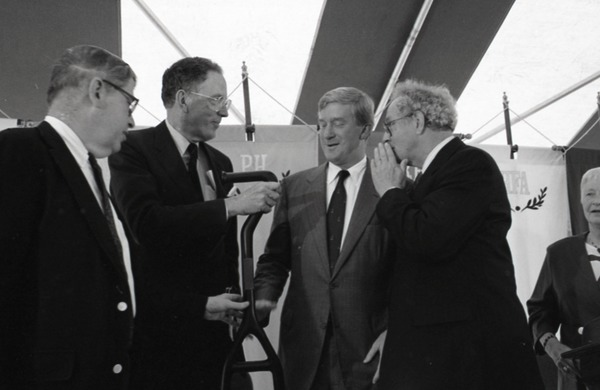Ceremonial groundbreaking for the Conte Center: Gov. William Weld, UMass Amherst             Provost Richard O'Brien, Corrine Conte, and unidentified man preparing for ceremonial             first shovel, July 30, 1991